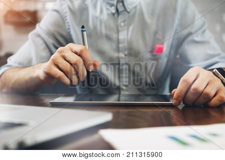 Young Businessman Holds A Stylus In His Hand And Works On Tablet. Tablet On A Wooden Table. Creative
