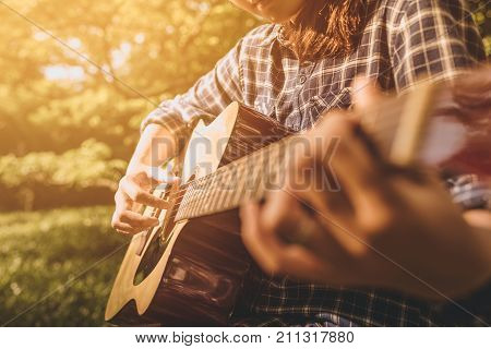 Female fingers playing guitar outdoor in summer park. Musician woman and her guitar in nature park Practice guitar. vintage tone. playing guitar. playing guitar park. playing guitar classic. playing guitar chord. playing guitar wood.  playing guitar woman