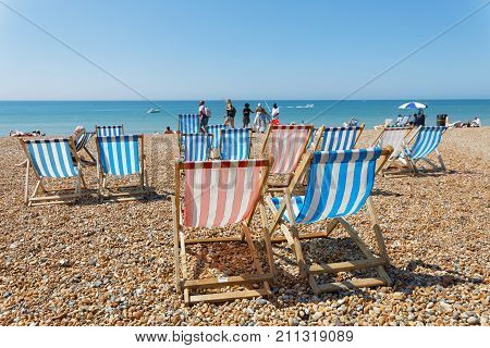 BRIGHTON GREAT BRITAIN - JUN 17 2017: Classic blue and red deckchairs and people sunbathing on the pebble beach. Blue sky and sunny. No people and blue sky. June 17 2017 in Brighton Great Britain