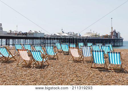 BRIGHTON GREAT BRITAIN - JUN 17 2017: Classic empty deckchairs on the pebble beach at the Brighton pier a sunny day. June 17 2017 in Brighton Great Britain