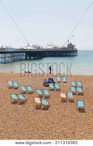 BRIGHTON GREAT BRITAIN - JUN 17 2017: Classic deckchairs on the pebble beach at the Brighton pier a sunny day. June 17 2017 in Brighton Great Britain