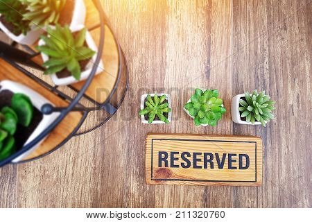 reserved sign on top of a wooden table in a restaurant reservation seat at restaurant for dating on celebrate day concept restaurant with reserved on table decorate with small cactus
