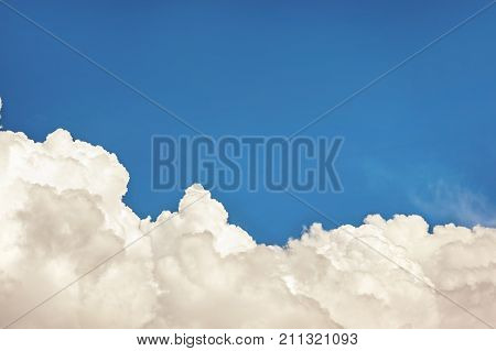 White cumulus congestus clouds on blue sky background. Vibrant multicolored outdoors horizontal image with vintage filter.Copy space.
