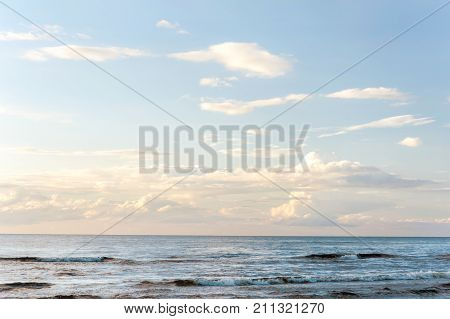 Landscape with white fleecy clouds above the sea on blue sky background. Vibrant multicolored outdoors horizontal image with copy space. Baltic states Latvia.
