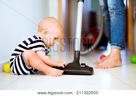 Unrecognizable young mother with a baby son doing housework. Beautiful woman and baby boy hoovering.