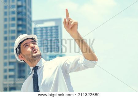 Engineer look to target and point direction by hand in city outdoor on building background. concept of target business goal and future company.