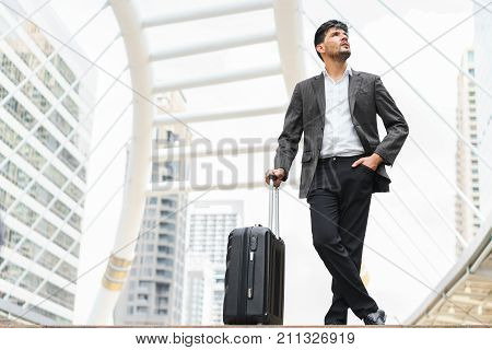 Handsome businessman standing and holding luggage with a look up on sky in city on building background concept of change life and work life balance.
