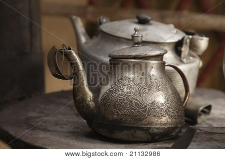 old teapot and kettle in a kyrgyz yurt kitchen, shallow dof poster