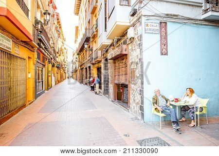 ZARAGOZA, SPAIN - August 20, 2017: View on the narrow street with elder couple sitting at the bar in the old town of Zaragoza city in Spain
