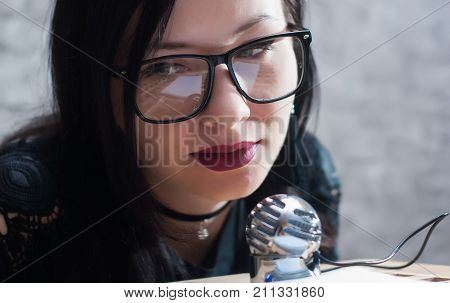 Cute girl in glasses conducts a podcast, closeup portrait of the girl blogger