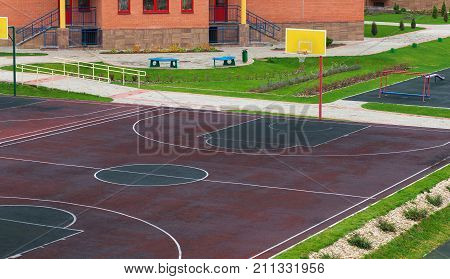 Schoolyard with a playground for basketball. Doing sports at school