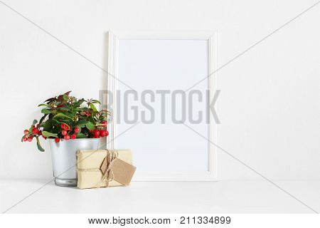 White blank wooden frame mockup with potted red teaberry plant and package with a gift tag on the white table. Styled stock feminine photography. Home decor, Christmas winter concept.