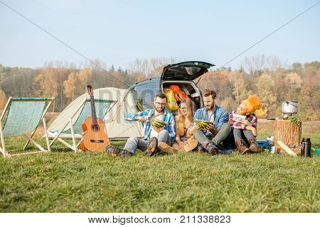 Multi ethnic group of friends having a picnic, eating watermelon, sitting in a row at the camping with tent, car and hiking equipment near the lake