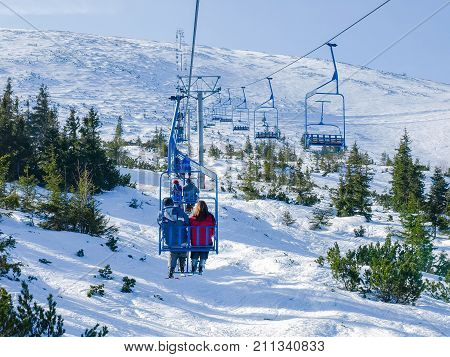 Two-person chair lift above of sparse growth of trees on ski resort Jasna in Slovakia