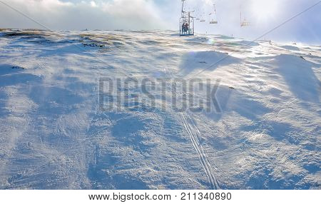 Top view of the mountain with compacted snow from chairlift on ski resort on a windy winter day