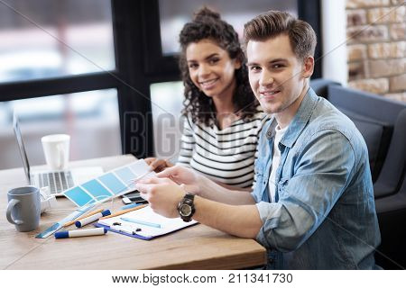 Studentship. Nice happy energetic girl and boy sitting at the table having cups and a laptop on it and smiling while the man holding a sheet of paper poster