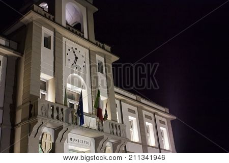 Front view of an Italian town hall (Porto Viro) in Veneto resumed at night with lit lights.