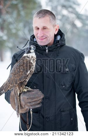 Man holding a falcon on his arm