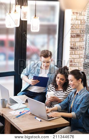 Nice atmosphere. Happy vigorous aspiring smiling man and two girls sitting at the table and talking while one girl working on the laptop and another holding a cup