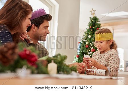 Cute Little Girl With Parents Reading Her Christmas Wish List