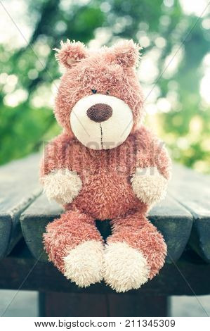 Awaiting for owner. Lonely sad forgotten teddy bear toy on wooden table in the park. Vintage filter. Outdoors.