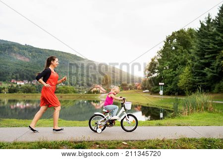 Young beautiful mother with her cute little daughter in nature by the lake. Daughter is cycling and smilling, mother is running.