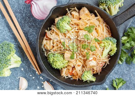 Fried vegan rice noodles with tofu and broccoli top view dark background. Healthy vegan food concept.