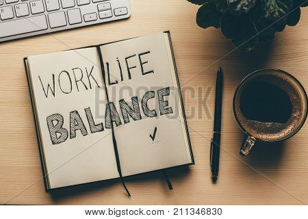 Work Life Balance - handwrite words in open notebook, pen, cup of coffee, top view of working place, retro toned. Lifestyle success strategy concept