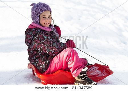 A cute little girl is sledding down the hill. Kids winter activities. Child in casual warm clothes playing winter games on Christmas holidays. Outdoors games