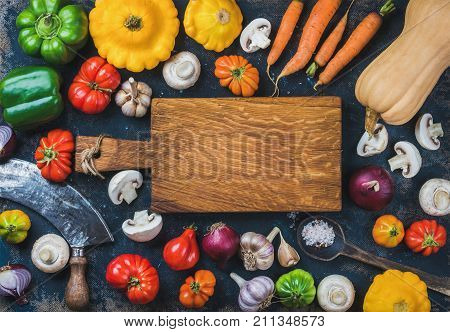 Tomatoes, onions, mushrooms, carrots, pumpkin, patissons, garlic, spices and knives on dark blue grunge plywood background with wooden chopping board in center. Top view, copy space poster