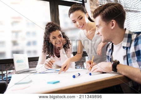 Making a drawing. Happy promising young man and two ladies making a technical drawing and a girl holding compasses and a man holding a pencil while looking at each other and smiling
