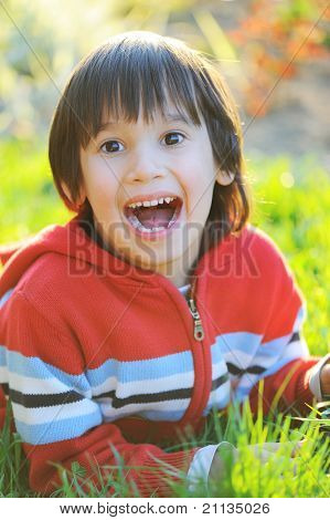 Little cute boy laying on morning summer grass with natural beautiful light