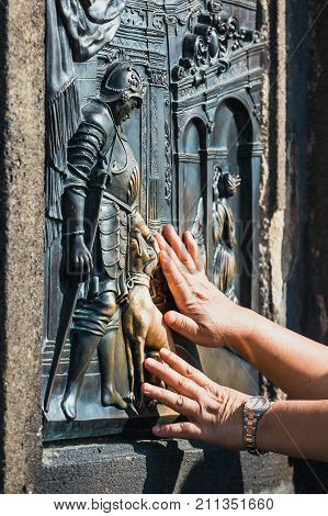 The bas-relief on the Charles Bridge in Prague touching the dog's sculpture for luck and loyalty