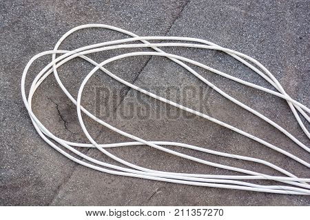 Close up image white power cord or wire on grey asphalt background