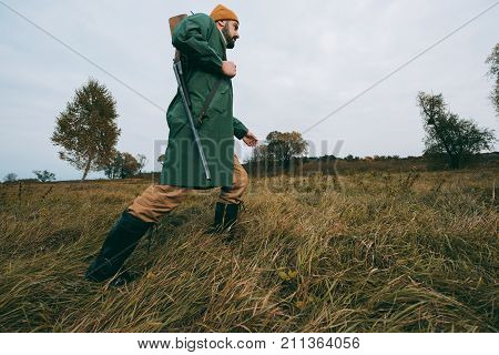 Hunter Going With Gun In Field