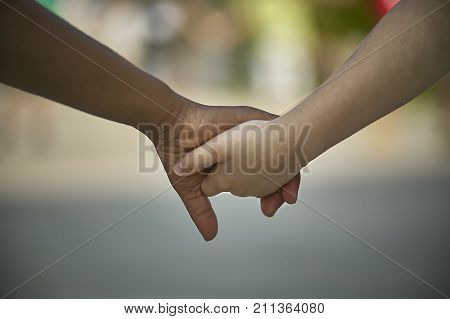 Hands of children shaking one of the caucasian or white complexion the other black. Symbol of inertness and equality between the races.