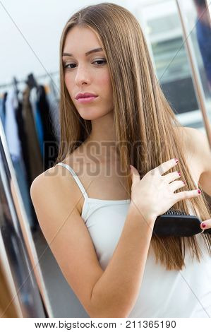 Beautiful Young Woman Brushing Her Long Hair In Front Of Her Mirror.