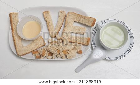 Love breakfast create idea from whole wheat bread and sweetened condensed milk serve with Tofu green tea milk in ceramic white cup isolate on wood chair.