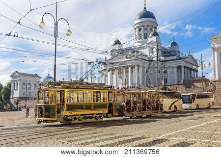 HELSINKI FINLAND - JULY 16 2016: Tram passing by Helsinki Senate Square (Senaatintori) with Helsinki Cathedral in background. Helsinki.