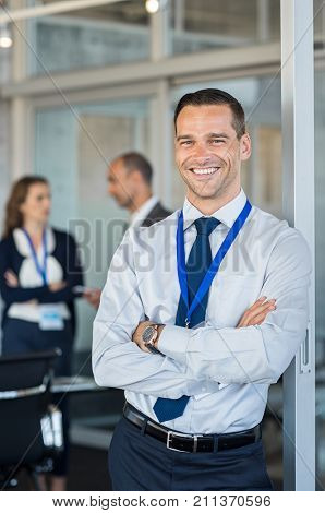 Smiling businessman with crossed arms looking at camera. Successful business man in formal wearing badge during a seminar. Happy proud businessman during a meeting with colleagues in background.