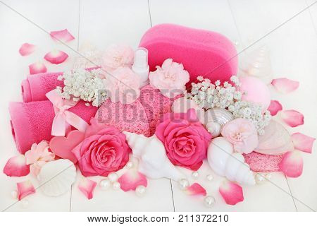 Spa and bathroom beauty treatment products with pink carnation flowers, himalayan  salt, heart shaped soaps, body lotion, sponges and flannels  with decorative hells and pearls on white wood.