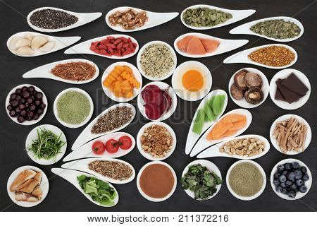 Super foods to boost brain power on slate background. Health food concept high in omega 3 fatty acids, vitamins, minerals, antioxidants and anthocyanins. Top view.