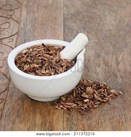 White willow bark herb used in herbal medicine and has pain relieving and anti inflammatory properties similar to aspirin in its effects, in a mortar with pestle on rustic wood background. Salix alba.