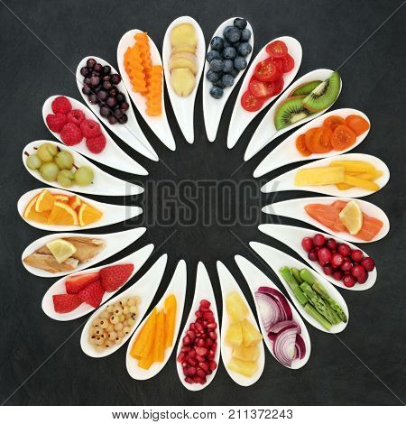Health food with vegetables, fruit and fish, super foods beneficial for a healthy heart and high in omega 3 fatty acid, anthocyanins, fiber, antioxidants and vitamins. On slate background top view.