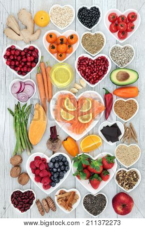 Healthy heart food with herbs, vegetables, fruit, fish, nuts, seeds, cereal and spice with super foods very high in omega 3 fatty acids, antioxidants, anthocyanins, vitamins and minerals.
