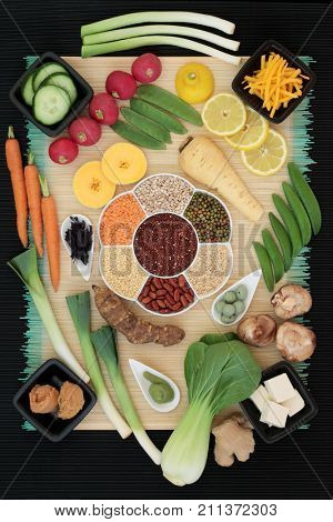 Fresh and dried macrobiotic food with tofu, vegetables, fruit, miso and wasabi paste, with foods high in protein, antioxidants, vitamins and minerals. On bamboo and black ridged background, top view,