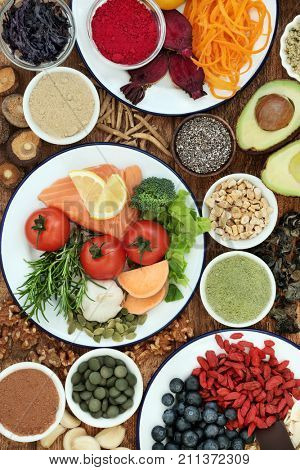Brain health food concept with fish, vegetables, seeds, nuts, berry fruit, herbs, supplement powders and tablets. Foods high in omega 3 fatty acids, vitamins, minerals, antioxidants and anthocyanins.