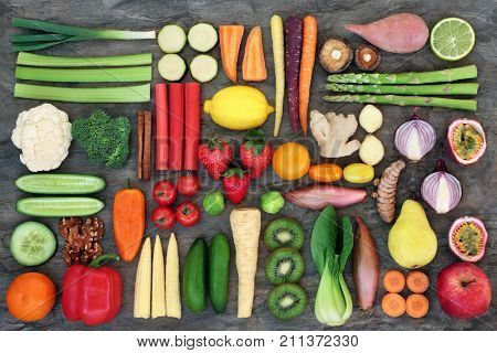 Super food for good health concept with fresh vegetables and fruit, nuts and spices with foods high in  anthocyanins, antioxidants, omega 3, dietary fibre, vitamins and minerals. Top view on marble.