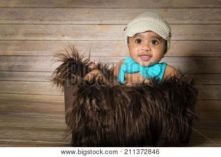 Infant dogla boy wearing hat and bow tie sitting in a fluffy furry basket wooden background modern studio shoot vintage look smiling