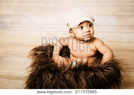 Infant dogla boy wearing hat sitting in a fluffy furry basket wooden background modern studio shoot vintage look